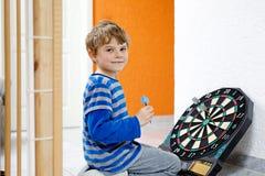Kleiner netter blonder Vorschulkinderjunge, der Pfeil, zuhause spielt Stockfotos