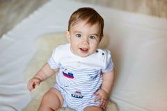 Kleiner netter entzückender kleiner blonder Junge in einem gestreiften bodykit sitti Stockbilder