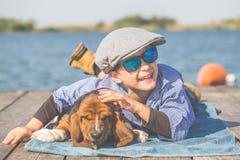 Kleiner netter Junge, der durch den Fluss mit seinem Hund liegt stockbild