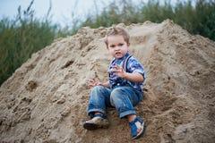 Kleiner netter Junge, der eine Achterbahn des Sandes auf die Unterseite reitet Gedächtniskindheit und sorgloses Stockfotografie