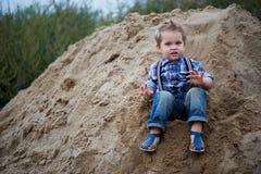 Kleiner netter Junge, der eine Achterbahn des Sandes auf die Unterseite reitet Gedächtniskindheit und sorgloses Lizenzfreies Stockfoto