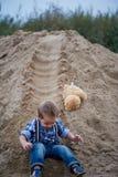 Kleiner netter Junge, der eine Achterbahn des Sandes auf die Unterseite reitet Gedächtniskindheit und sorgloses Stockbilder