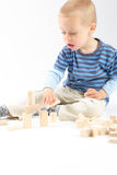 Kleiner netter Junge, der mit Bausteinen spielt Lokalisiert auf Weiß Stockfotos