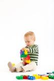 Kleiner netter Junge, der mit Bausteinen spielt Lokalisiert auf Weiß Lizenzfreies Stockfoto