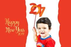 Kleiner netter Junge, der mit ` guten Rutsch ins Neue Jahr-` u. -c$lächeln aufwirft Lizenzfreies Stockbild