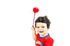 Kleiner netter Junge, der mit Liebessymbol u. -c$lächeln aufwirft Lizenzfreie Stockfotografie