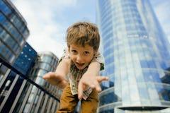 Kleiner netter Junge, der nahes Geschäftsgebäude steht Stockfotografie