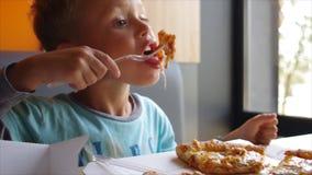 Kleiner netter Junge, der Pizza mit Appetit isst stock video