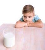 Kleiner netter Junge in einem blauen T-Shirt betrachtet ein transparentes Glas voll geschmackvollen Milch Stndings lokalisiert au stockfotos