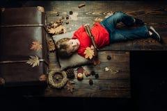 Kleiner netter Junge liegt auf einem Bretterboden mit Herbstlaub und las Buch Kind, das im Herbst spielt Die größten Rabatte stockbild