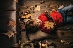 Kleiner netter Junge liegt auf einem Bretterboden mit Herbstlaub und las Buch Kleines Kinderjunge liegt auf warme umfassende Träu stockfotos