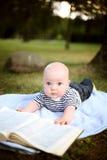 Kleiner netter Junge liest ein Buch im Sommerpark lizenzfreie stockbilder