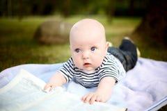 Kleiner netter Junge liest ein Buch im Sommerpark lizenzfreies stockbild