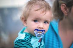 Kleiner netter Junge mit einem Babyfriedensstifter in seinem Mund in seinem Mutter ` lizenzfreie stockfotos