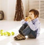Kleiner netter Junge zu Hause, der grünen Apfel isst Stockfotos