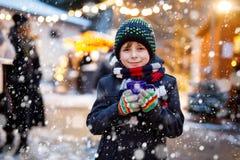 Kleiner netter Kinderjunge, der heißen Kinderdurchschlag oder -schokolade auf deutschem Weihnachtsmarkt trinkt Glückliches Kind a stockbilder
