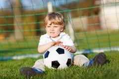 Kleiner netter Kinderjunge spielenden Fußballs 4 mit Fußball auf Feld, draußen Stockfoto