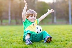 Kleiner netter Kinderjunge spielenden Fußballs 4 mit Fußball auf Feld, draußen Lizenzfreie Stockfotografie