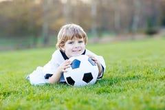 Kleiner netter Kinderjunge spielenden Fußballs 4 mit Fußball auf Feld, draußen Stockbilder