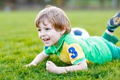 Kleiner netter Kinderjunge spielenden Fußballs 4 mit Fußball auf Feld, draußen Stockbild
