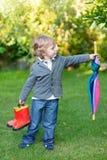 Kleiner netter Kleinkindjunge mit buntem Regenschirm und Stiefeln, outdoo Stockfotos