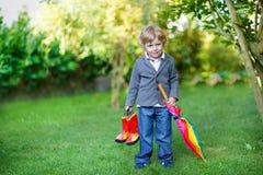 Kleiner netter Kleinkindjunge mit buntem Regenschirm und Stiefeln, outdoo Stockbilder