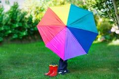 Kleiner netter Kleinkindjunge mit buntem Regenschirm und Stiefeln, outdoo Lizenzfreie Stockfotografie