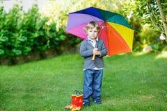 Kleiner netter Kleinkindjunge mit buntem Regenschirm und Stiefeln, outdoo Stockfotografie