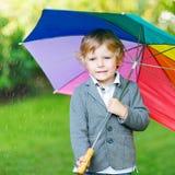 Kleiner netter Kleinkindjunge mit buntem Regenschirm und Stiefeln, outdoo Lizenzfreie Stockbilder