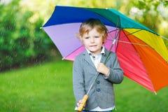 Kleiner netter Kleinkindjunge mit buntem Regenschirm und Stiefeln, outdoo Stockfoto