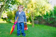 Kleiner netter Kleinkindjunge mit buntem Regenschirm und Stiefeln, outdoo Stockbild