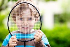 Kleiner netter lustiger Kinderjunge, der Badminton im inländischen Garten spielt Lizenzfreies Stockfoto