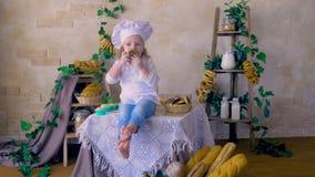Kleiner netter Mädchenkoch, der im Küchenlächeln, spielend mit Lebensmittel sitzt stock video footage