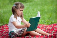 Kleiner netter Mädchenvorschüler mit Buch im Park Stockfotografie