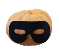 Kleiner orange Kürbis in der Maskeradeschablone Lizenzfreie Stockfotos