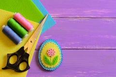 Kleiner Patchwork Ostereidekor, farbiger Threadsatz, Scheren, Filz bedeckt auf einem purpurroten hölzernen Hintergrund mit Kopien Stockfotografie