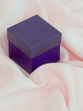 Kleiner purpurroter Kasten auf rosafarbener Seide Stockbild