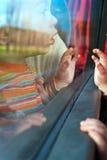 Kleiner Reisender, der aus Busfenster heraus schaut Lizenzfreies Stockbild