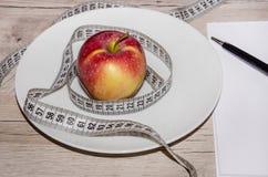 Kleiner, roter Apfel in einer weißen Platte, Notizbuch und Stift auf dem Tisch lizenzfreie stockfotos