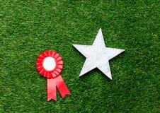Kleiner roter Siegerpreis und Sterngeschenk Lizenzfreie Stockfotografie