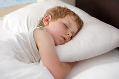 Kleiner süßer Kleinkindjunge, der in seinem Bett schläft Lizenzfreie Stockfotos