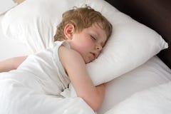 Kleiner süßer Kleinkindjunge, der in seinem Bett schläft Lizenzfreies Stockbild