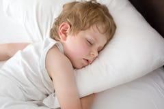 Kleiner süßer Kleinkindjunge, der in seinem Bett schläft Lizenzfreie Stockbilder