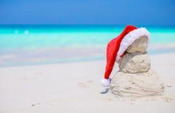 Kleiner sandiger Schneemann mit roter Santa Hat auf Weiß Lizenzfreies Stockfoto