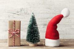 Kleiner Santa Claus-Hut, Geschenk und dekorativer Tannenbaum auf hölzernem rustikalem Hintergrund Weihnachts- und des neuen Jahre Stockfotos