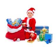 Kleiner Santa Claus-Junge mit Geschenken Stockfotos