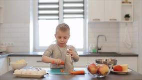 Kleiner schöner kaukasischer Junge mit großen blauen Augen kochend in der hellen Küche Er ist reibt eine Karotte stock video footage