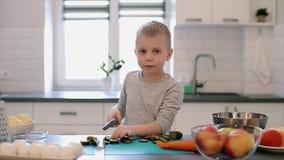 Kleiner schöner kaukasischer Junge mit großen blauen Augen kochend in der hellen Küche stock video footage