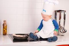Kleiner Schätzchenchef im Kochhut, der Pfannkuchen bildet Stockfotografie