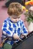 Kleiner schöner Junge, der ein Kabel in einen Sprecher verlegt Lizenzfreies Stockfoto